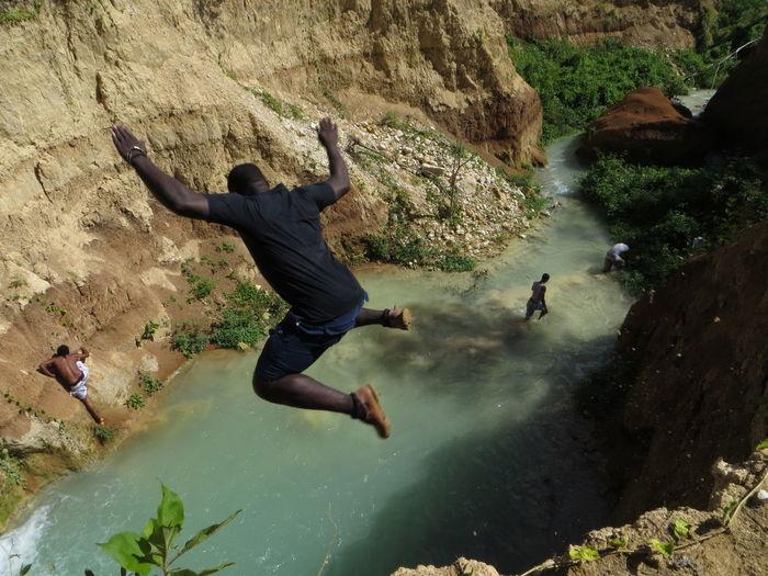 Man jumping off rock at shore