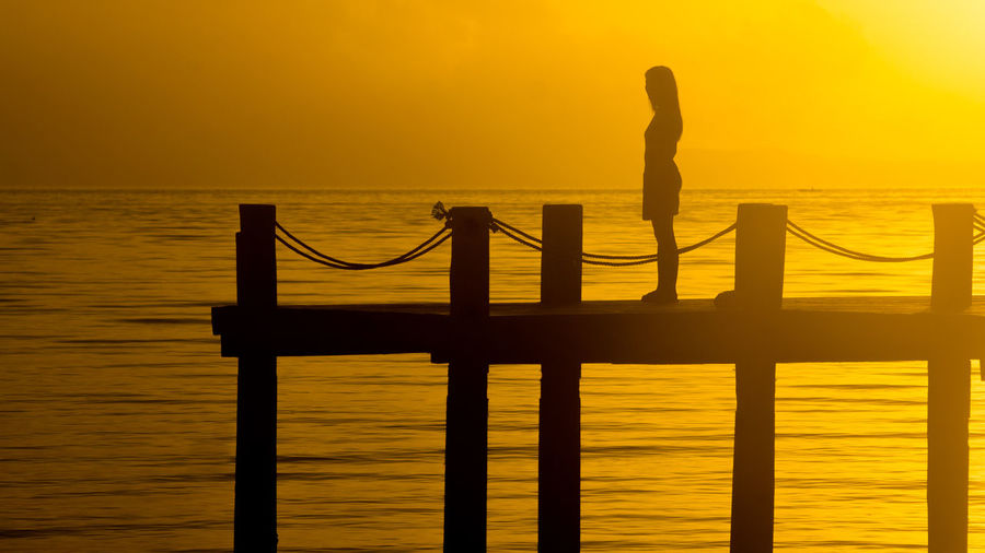 Woman silhouette standing on island dock at sunset Backpacking Boat Dock Contemplative Digital Nomad Emotion Emotional Fishing Dock Fishing Pier Independence Introspection Island Life Island Living Living The Dream Lonely Girl One Person Orange Sky Sad Girl Sad Woman Seascapes Solo Travel Solo Traveller Solotraveler Sunset Silhouette Sunset Silouhette Thinking About Life