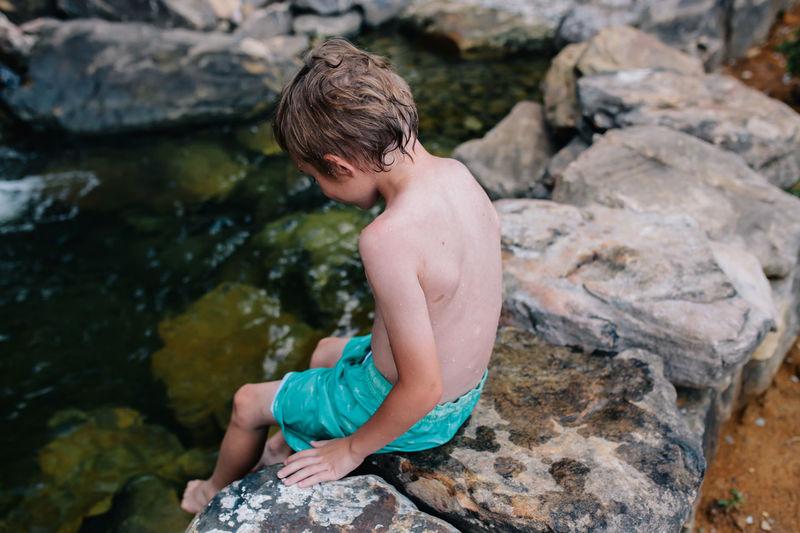 Rear view of shirtless boy on rock