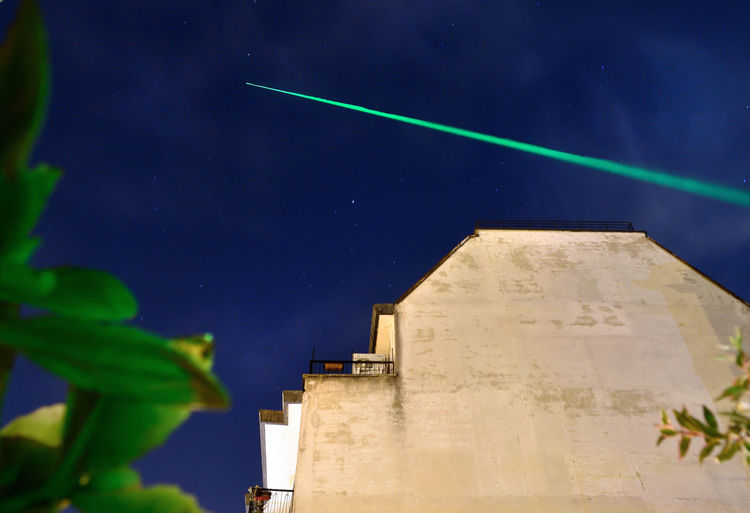 Low Angle View Of Laser Light Over Building Against Sky At Dusk