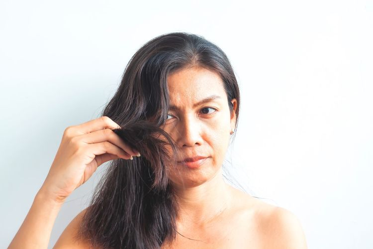 Middle aged Asian woman worried about damaged hair. Healthy and beauty concept Human Hair Human Face Beautiful Woman Cut Out Adult Copy Space Long Hair Lifestyles White Background Black Hair Holding Hairstyle Young Adult Hair Indoors  Studio Shot Front View Portrait One Person Headshot Damaged Beauty Problem Diversity Imperfection Hair Fall Scalp Massage Itchy Worry Roots Of Hair