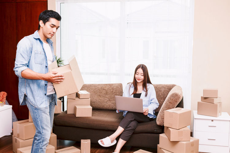 Couple with cardboard boxes in new home