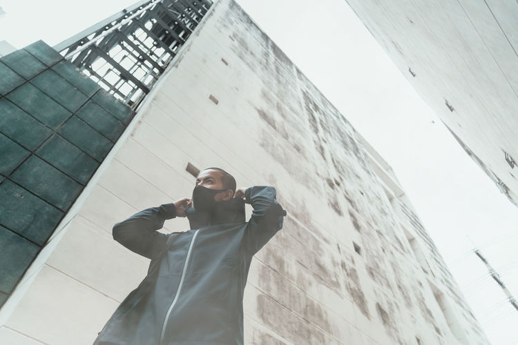 Low angle view of man standing by building