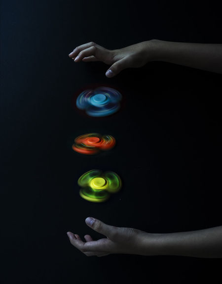 Fidget Spinner in actions Actions Black Background Blue Enjoyment Fidget Spinner Fingers Fun Green Color Hand Holding Hot Toys Human Finger Human Hand Multi Colored Red Release Tension Skill  Skillful Smart Spinning Style Toy Worldwide Games Yellow