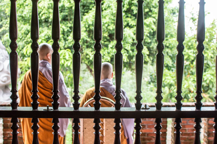Rear View Of Monks Seen Through Window At Temple