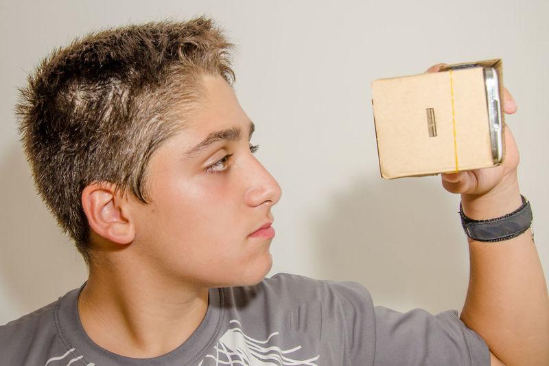 Close-up of boy gesturing while wearing virtual reality simulator