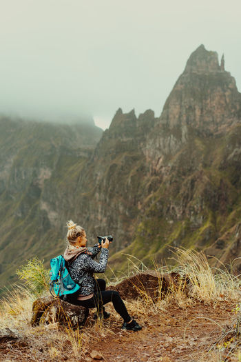 Rear view of woman photographing while sitting against mountain