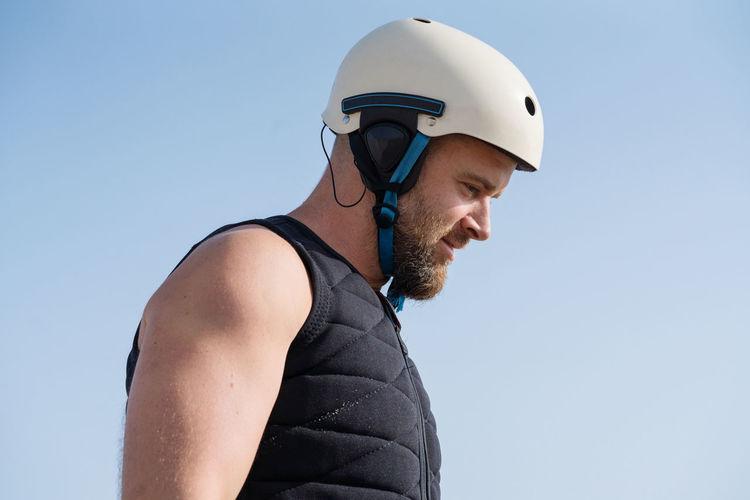 Low angle portrait man wearing helmet and life vest