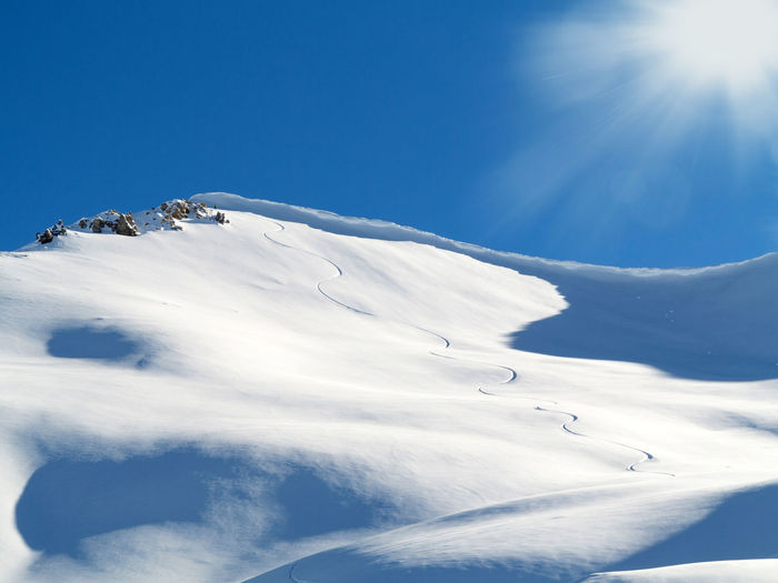 Scenic view of snowcapped mountains against blue sky on sunny day