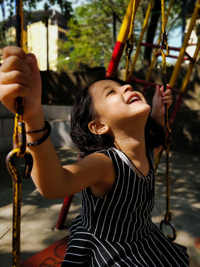 Girl playing on swing at playground