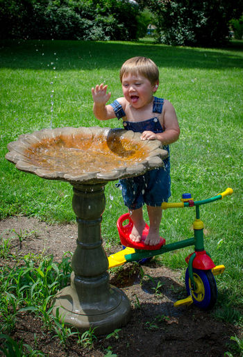 Toddler playing in a bird bath, stands on his tricycle to be a little taller Toddler  2 Years Old Boy Fun Child Happy Smiling Caucasian Childhood Home Outdoors Son Water Children Creativity Development Garden Game Creative Joy Kids person Imagination Little Male Learning Bird Bath Splash Standing On Bike Bike Bicycle Overalls Summertime Wet Messy Funny Excited Colorful Laughing Enjoyment barefoot Nature Full Length Day Boys Casual Clothing Innocence Splashing Playtime Seasonal