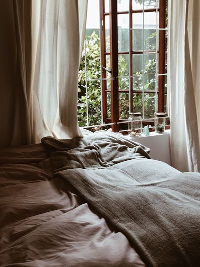 Close-up of bed by window at home