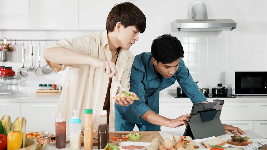 Friends standing on cutting board at home