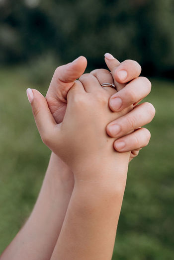 Clasped hands of woman outdoors