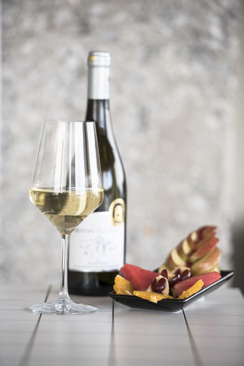 Wineglass and bottle with fruits on floor