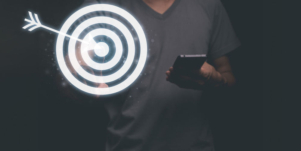 Midsection of man holding mobile phone while standing against black background