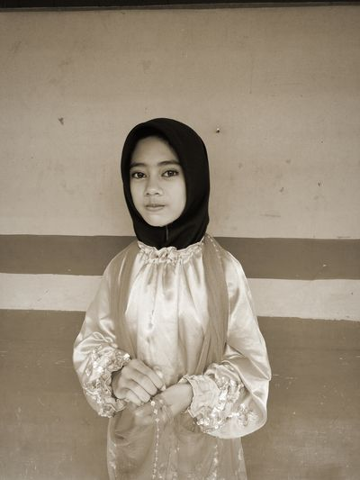 Portrait of young woman wearing hijab standing against wall