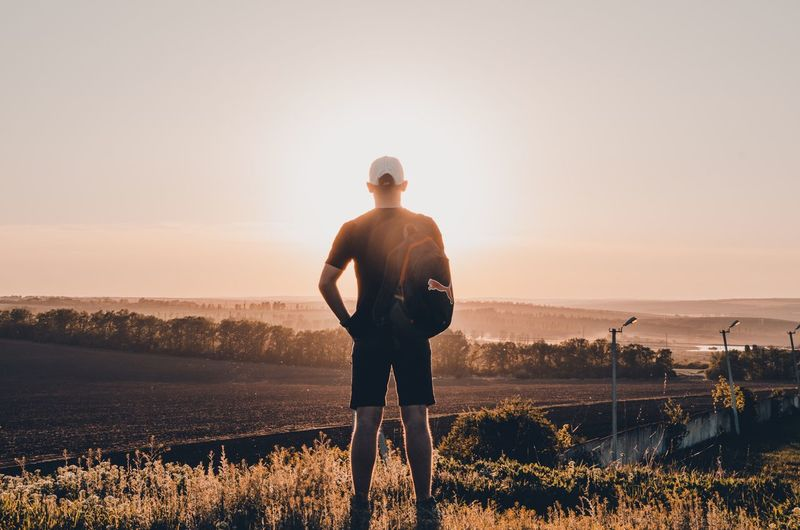 The man is looking far into the beautiful sunset Sky Sun Field Sunset Background View Landscape Sun Sky One Person Real People Sunset Water Standing Lifestyles Outdoors Three Quarter Length Beauty In Nature Land Copy Space Nature Scenics - Nature Rear View Leisure Activity Men Plant Sunlight
