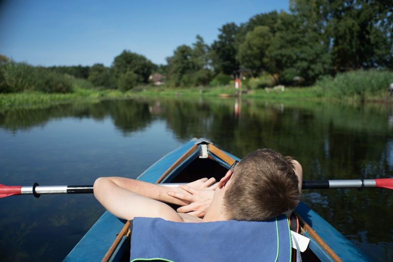 Rear View Of Men In Boat On Lake