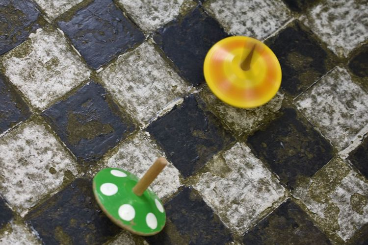 High angle view of spinning tops on floor
