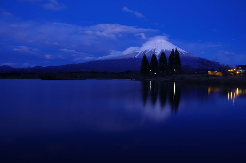 Scenic view of lake against blue sky at dusk