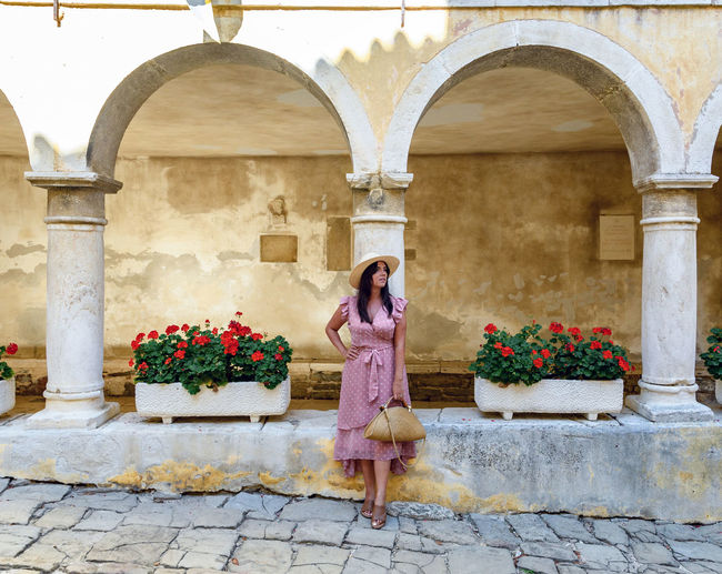 Young woman in pink summer dress standing in old town square.