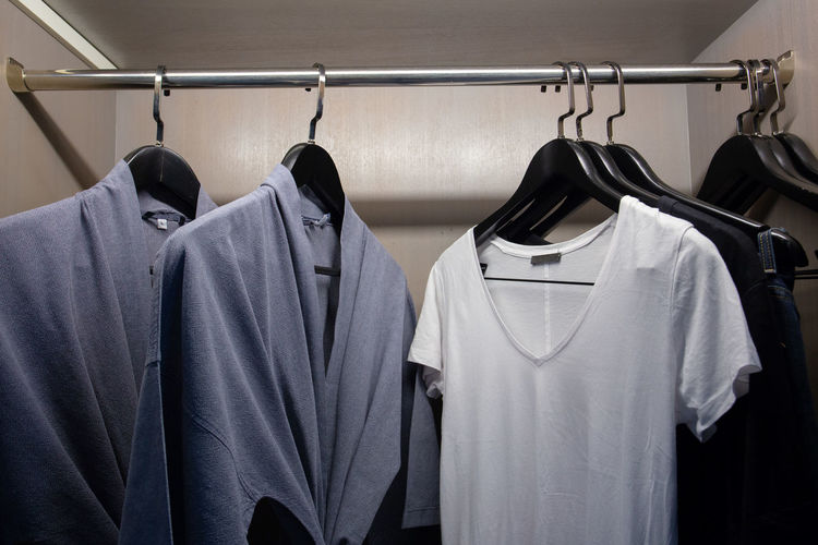 Close-up of clothes hanging on rack in shelf