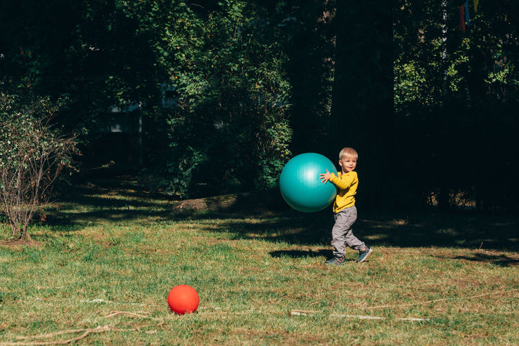 Side View Of Cute Boy Playing With Large Ball In Park