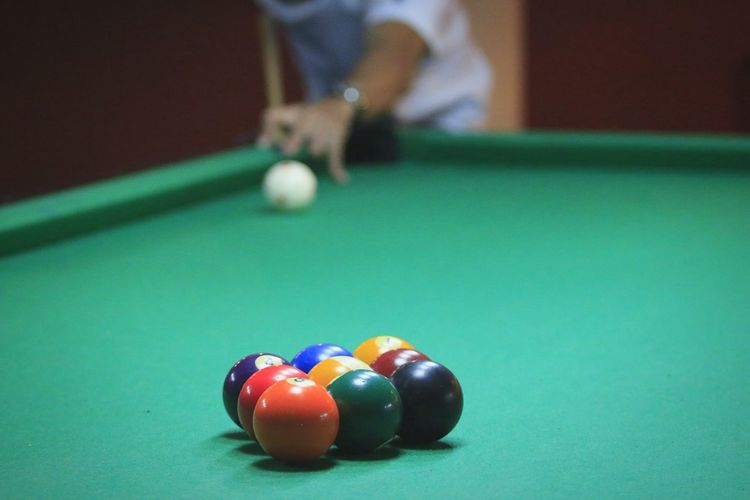 Midsection of man playing pool