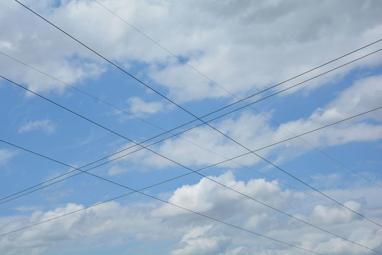 Low angle view of cables against cloudy sky