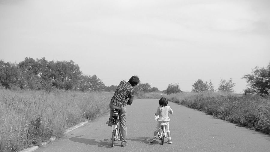 Father And Daughter Riding Bicycle On Road Amidst Field