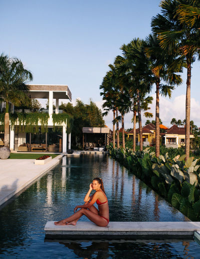 Woman at a luxury pool in Bali Tree Water Architecture One Person Built Structure Sitting Building Exterior Lifestyles Palm Tree Sky Full Length Swimming Pool Pool Leisure Activity Young Adult Real People Outdoors Villa Luxury Resort Bali Canggu INDONESIA Bikini Woman