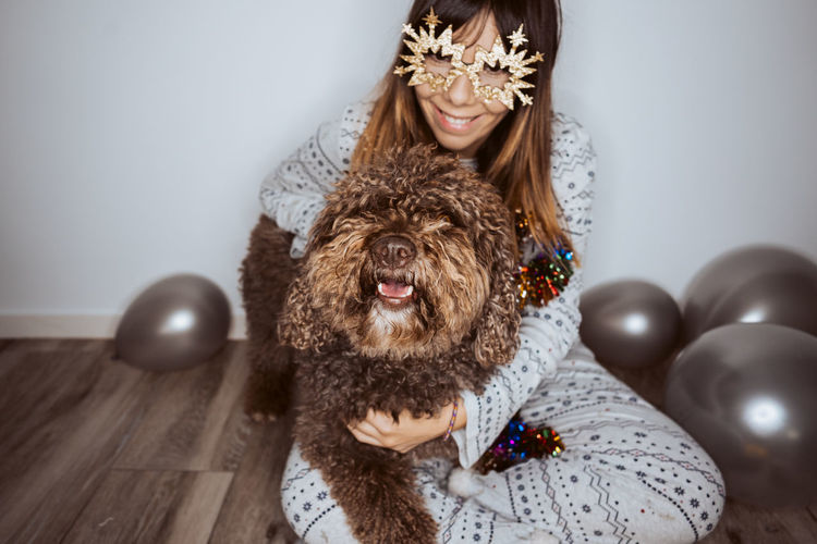 Smiling woman wearing mask sitting with dog and balloons on floor at home