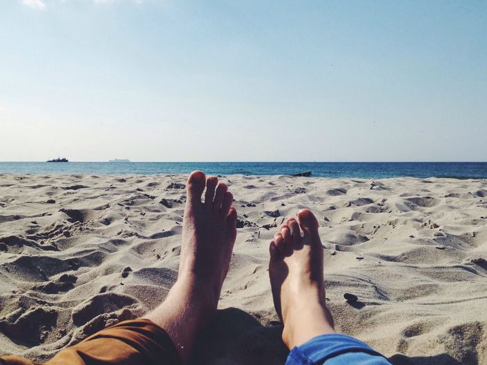 Low section of couple relaxing on sandy beach