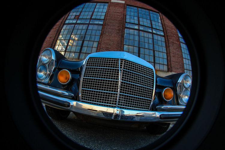Vintage car against building seen through circle shape window
