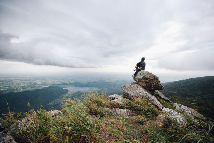 Hiker sitting on rocks against cloudy sky during foggy weather
