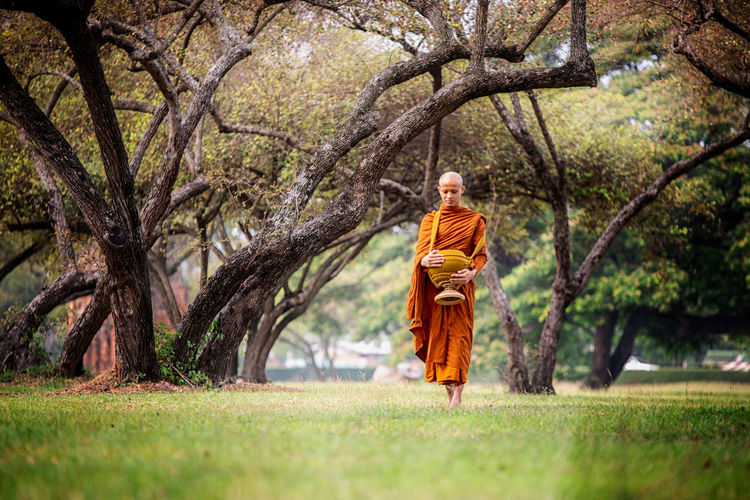 Full length of monk wearing traditional clothing walking in forest