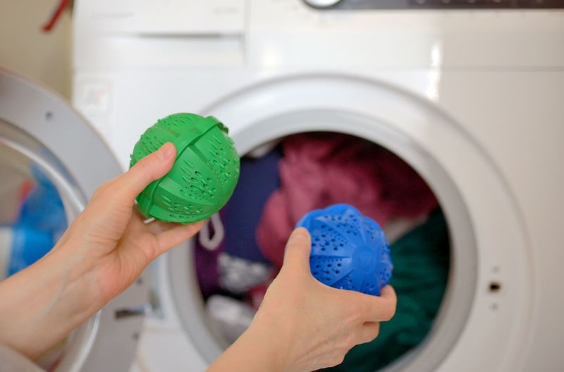 Cropped Hands Of Woman Putting Detergent In Washing Machine