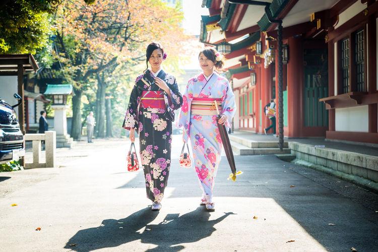 Women walking on footpath in city