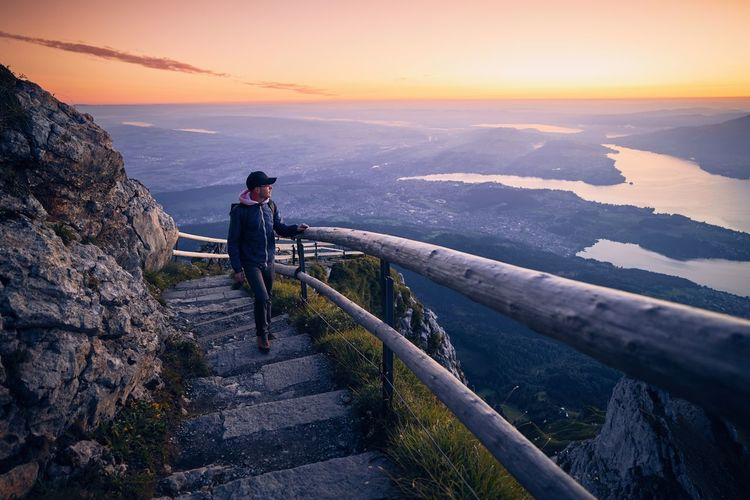 Man looking away while standing on steps against sky during sunset