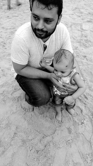 High angle view of father with baby boy on sand at beach
