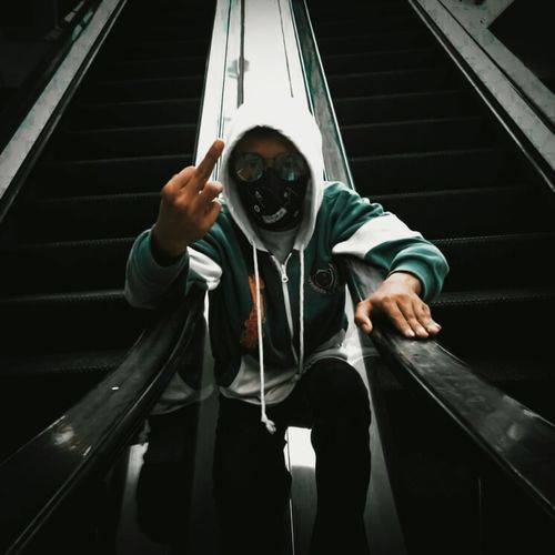 Portrait of man holding umbrella on staircase