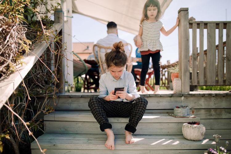 Full length of children sitting on staircase