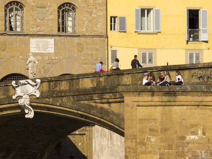 People At Ponte Santa Trinita Bridge Against Buildings