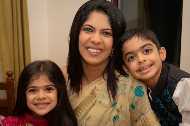 Portrait of smiling mother with daughter and son at home