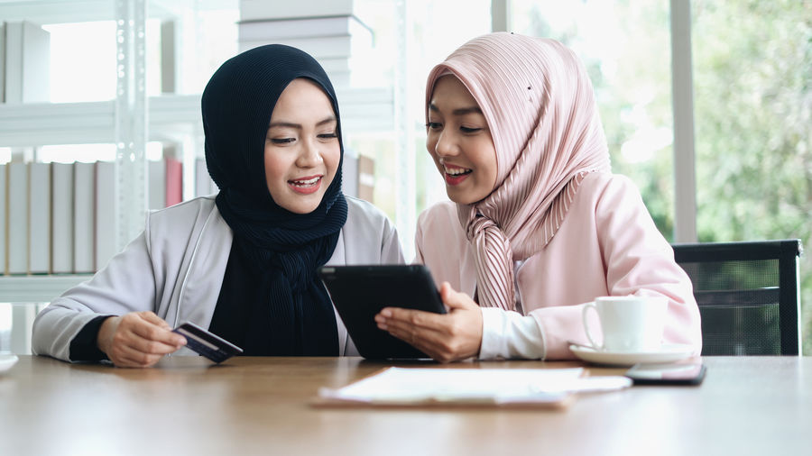 Young females wearing hijab shopping online while sitting in office