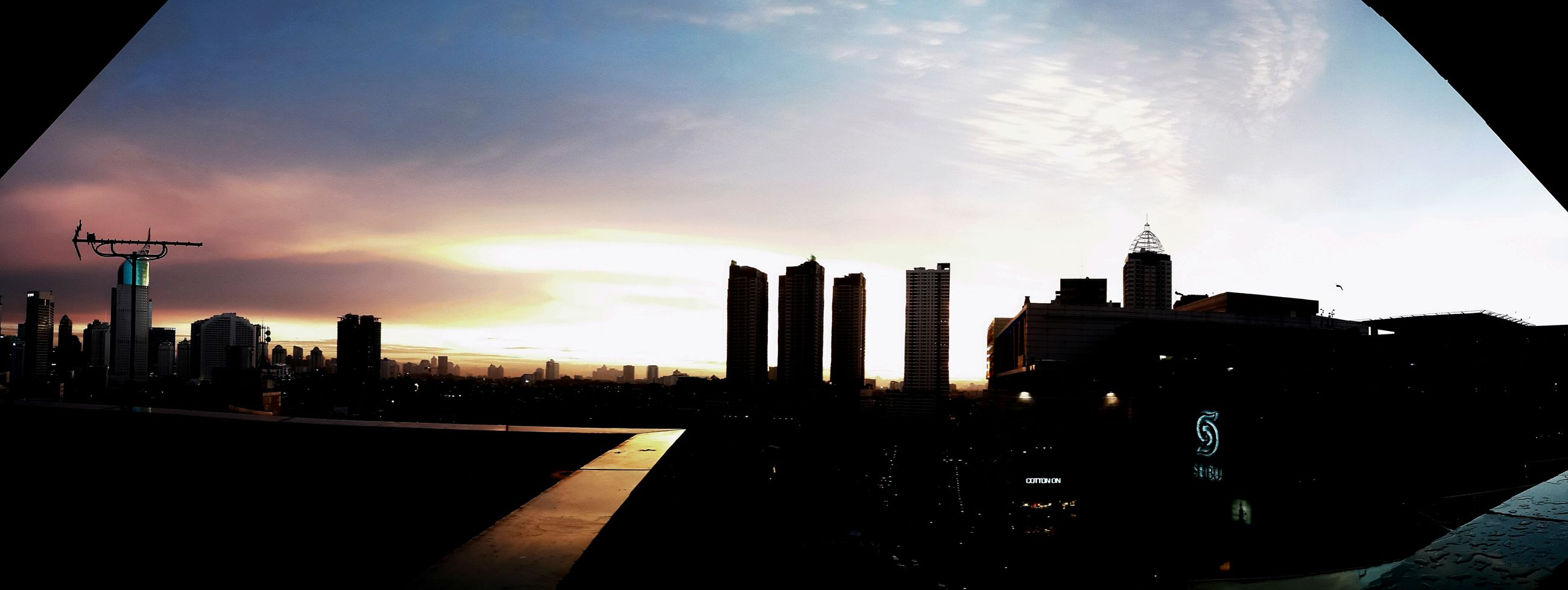 architecture, building exterior, built structure, sky, city, sunset, silhouette, skyscraper, cloud - sky, tower, tall - high, building, cloud, urban skyline, office building, cityscape, sunlight, low angle view, modern, cloudy