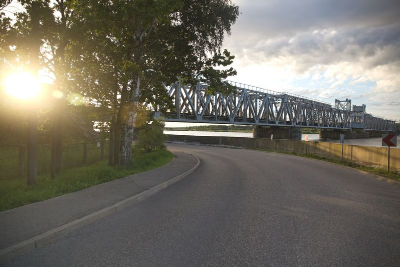 Curved Road Against Bridge Over The River