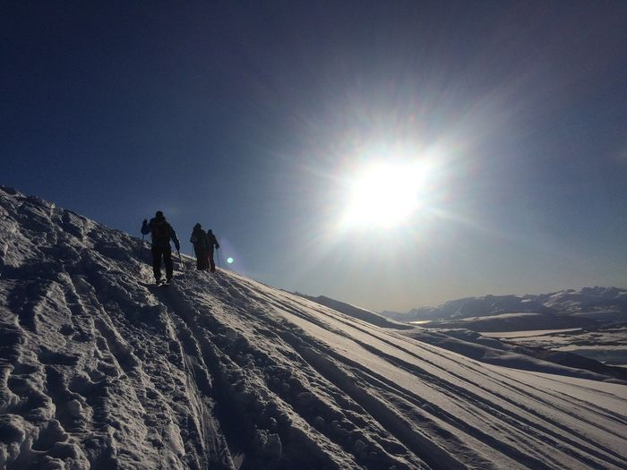 Winter Sunlight Sun Cold Temperature Snow Real People Leisure Activity Two People Mountain Adventure Beauty In Nature Clear Sky Lens Flare Lifestyles Nature Sunbeam Scenics Weather Sky Day