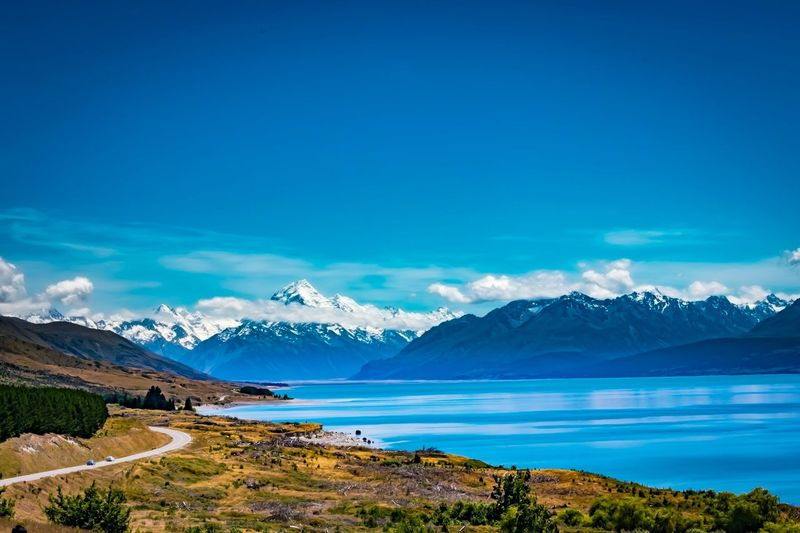 Scenic View Of River By Mountains Against Blue Sky